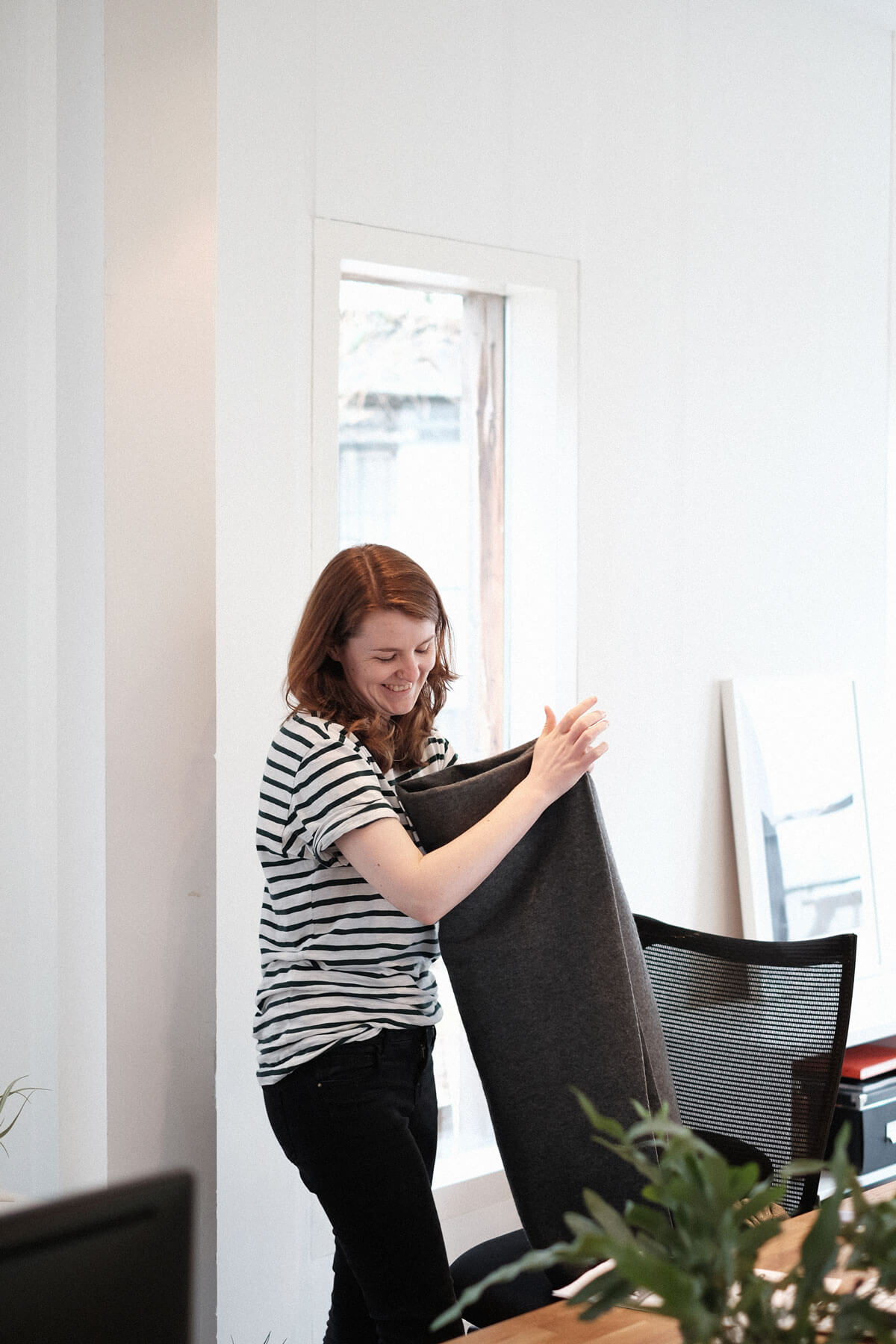 Woman folding a blanket in office