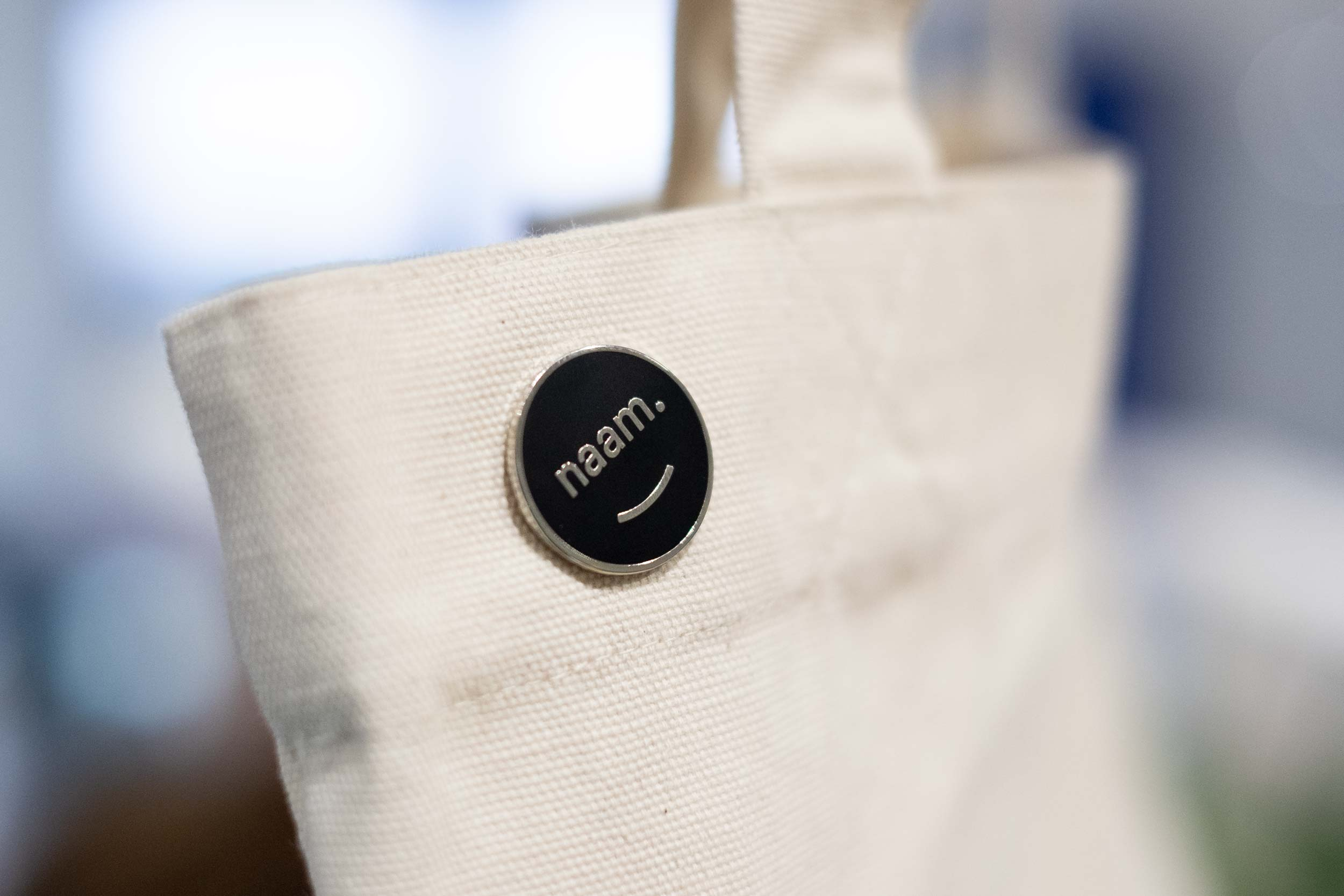 A canvas tote bag with a Naam logo enamel pin