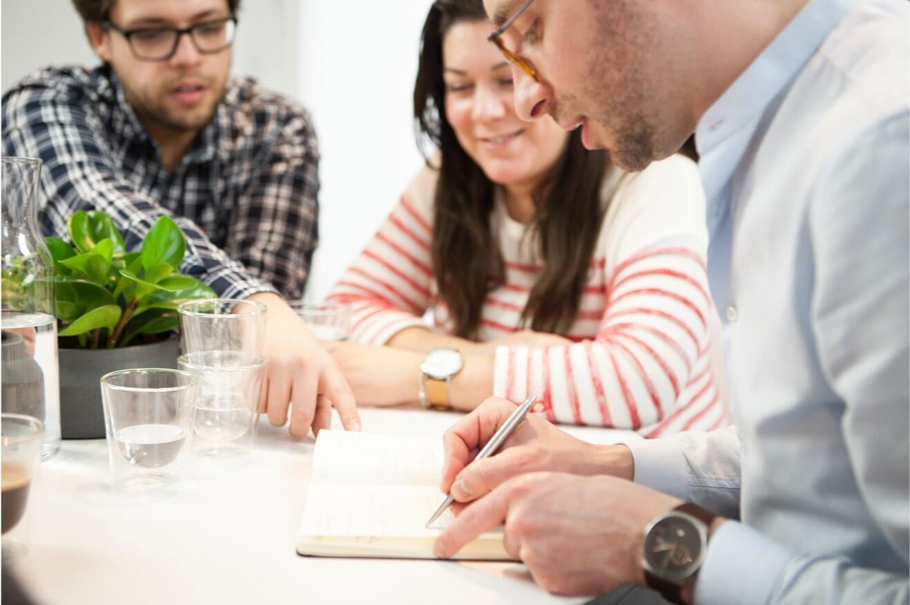 Drie mensen aan het schetsen aan een tafel